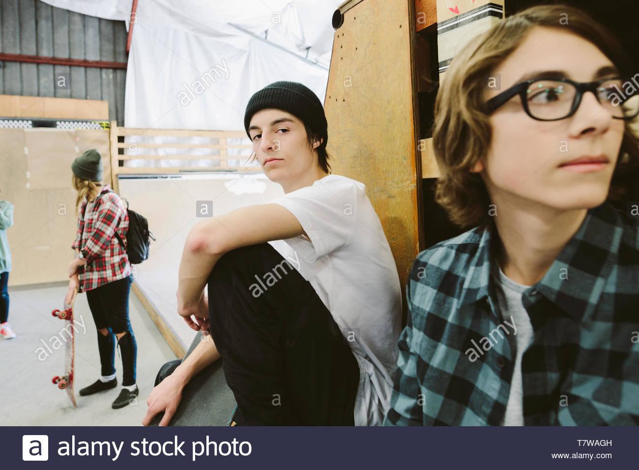 Portrait zuversichtlich, cooler Teenager an indoor Skatepark Stockbild