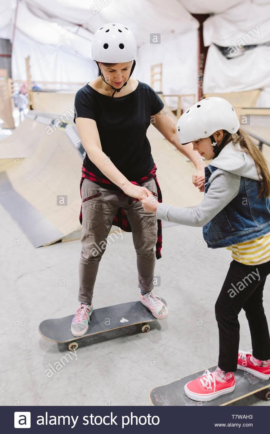 Mutter lehre Tochter an indoor Skatepark zu Skateboard Stockbild