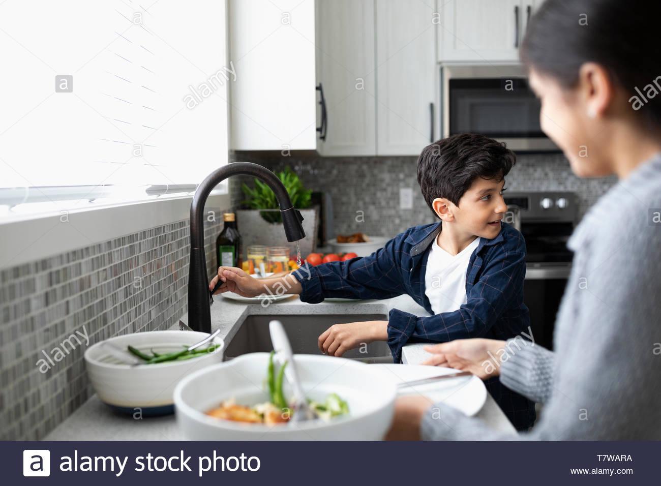 Bruder und Schwester tun Gerichte im Spülbecken Stockbild