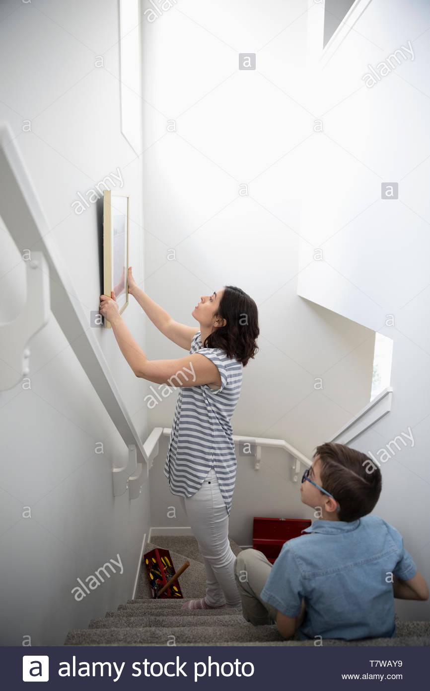 Sohn beobachten Mutter hängen Bild an der Wand über Treppen Stockbild