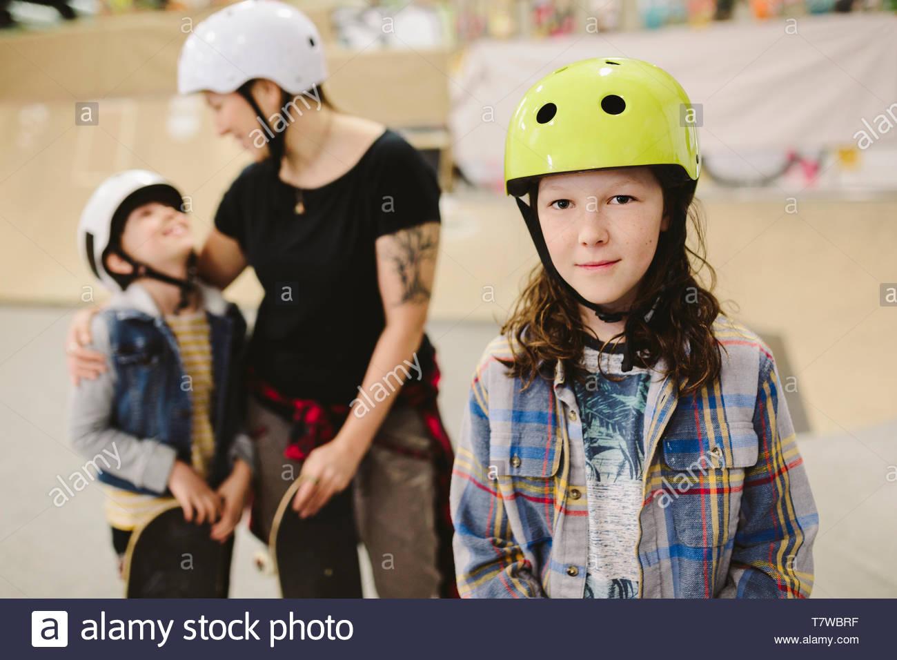 Portrait zuversichtlich Junge an indoor Skatepark mit Familie Stockbild