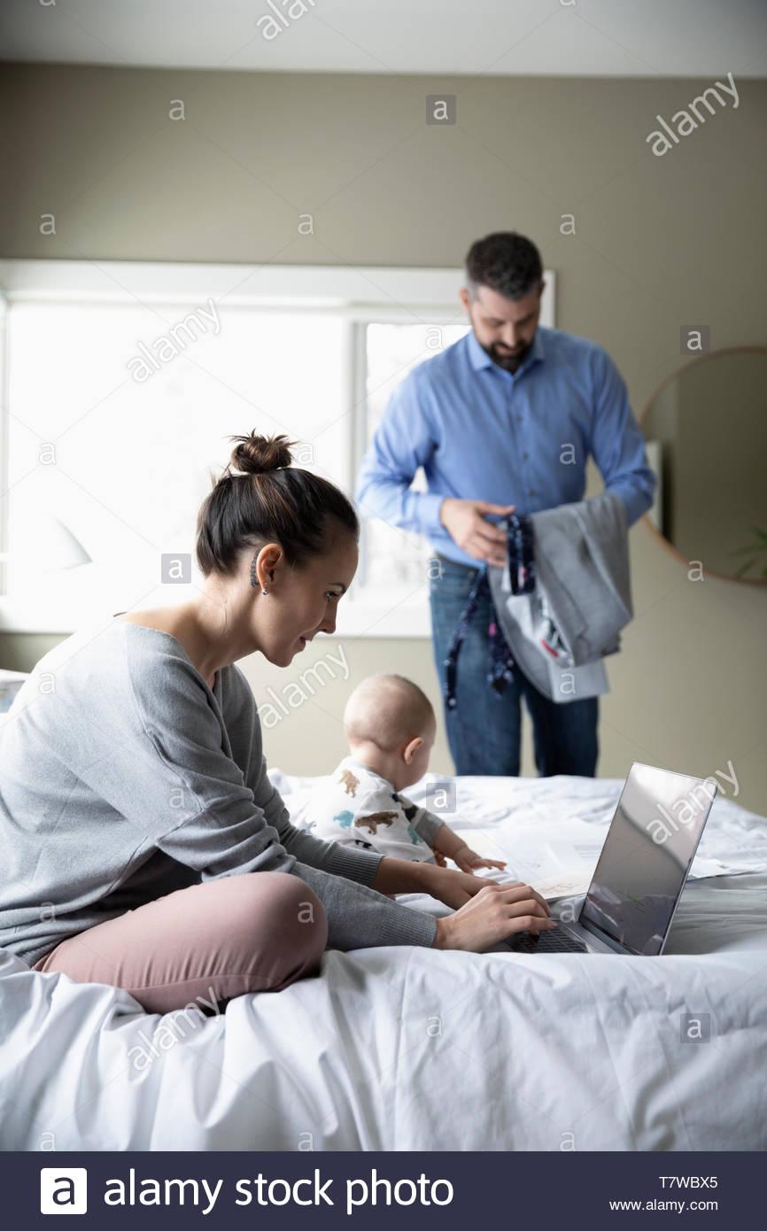 Eltern mit Babys, die von zu Hause aus arbeiten und sich für die Arbeit fertig im Schlafzimmer Stockbild