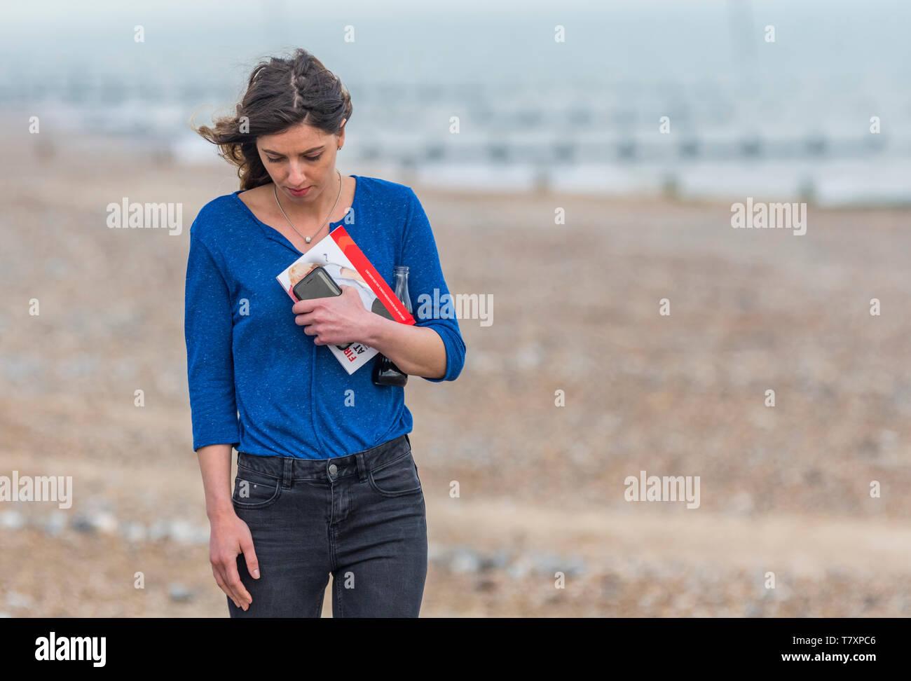 Junge Frau allein spazieren, beim Denken an einem Strand im Frühling. Einsame Frau alleine zu Fuß unterwegs. Zeit Konzept zu denken. Einsamkeit Konzept. Stockbild