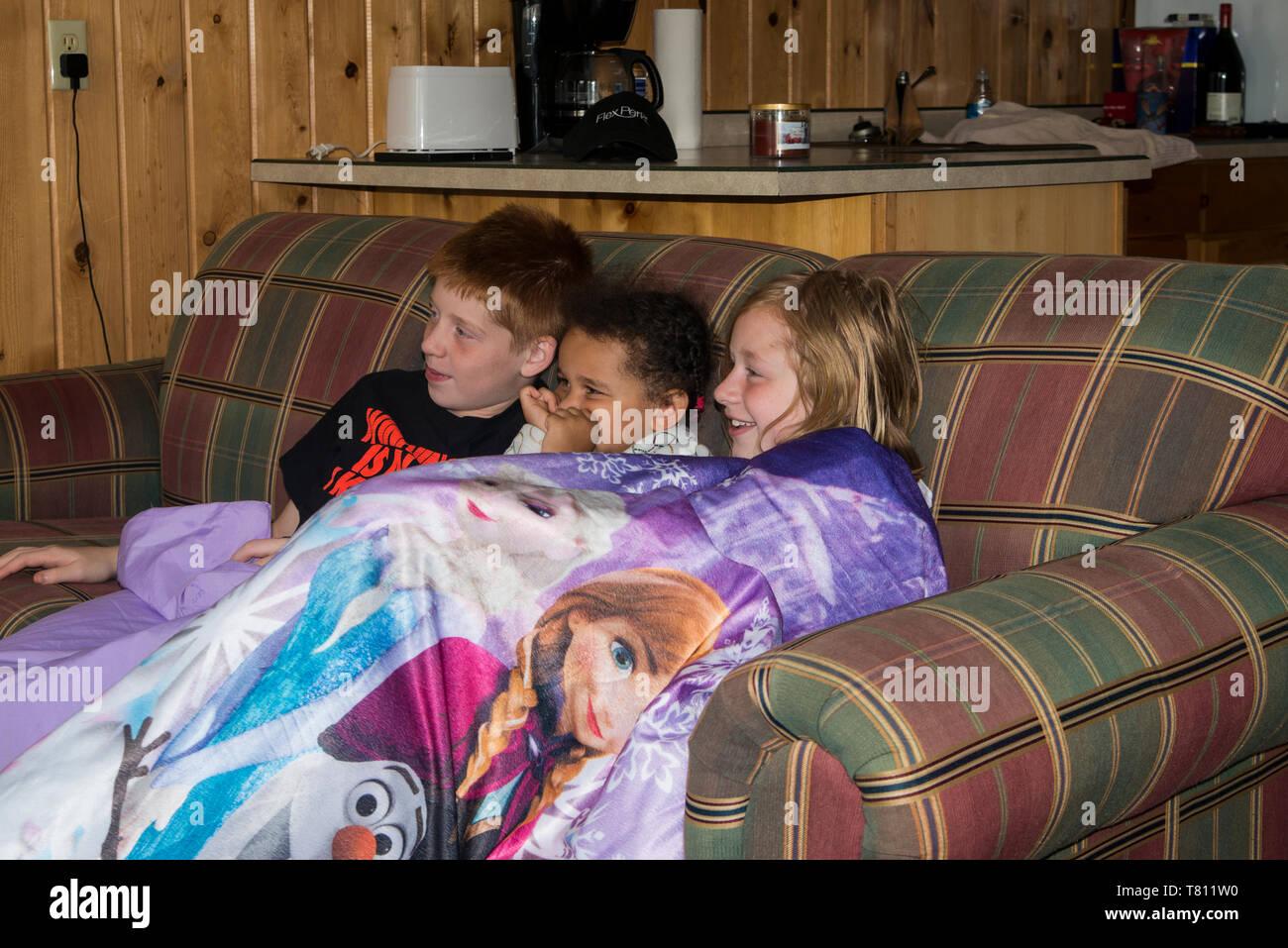 Naytahwaush; Minnesota. Drei Geschwister a scary movie zusammen beobachten. Stockbild