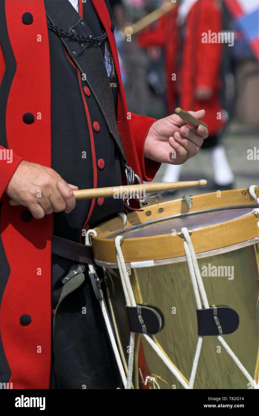 Ein Mann in einem historischen Kostüm spielen auf einem großen Snare Drum. Ein Mann in einem historischen Kostüm, der in einer großen Snare spielt. Werblista Stockbild