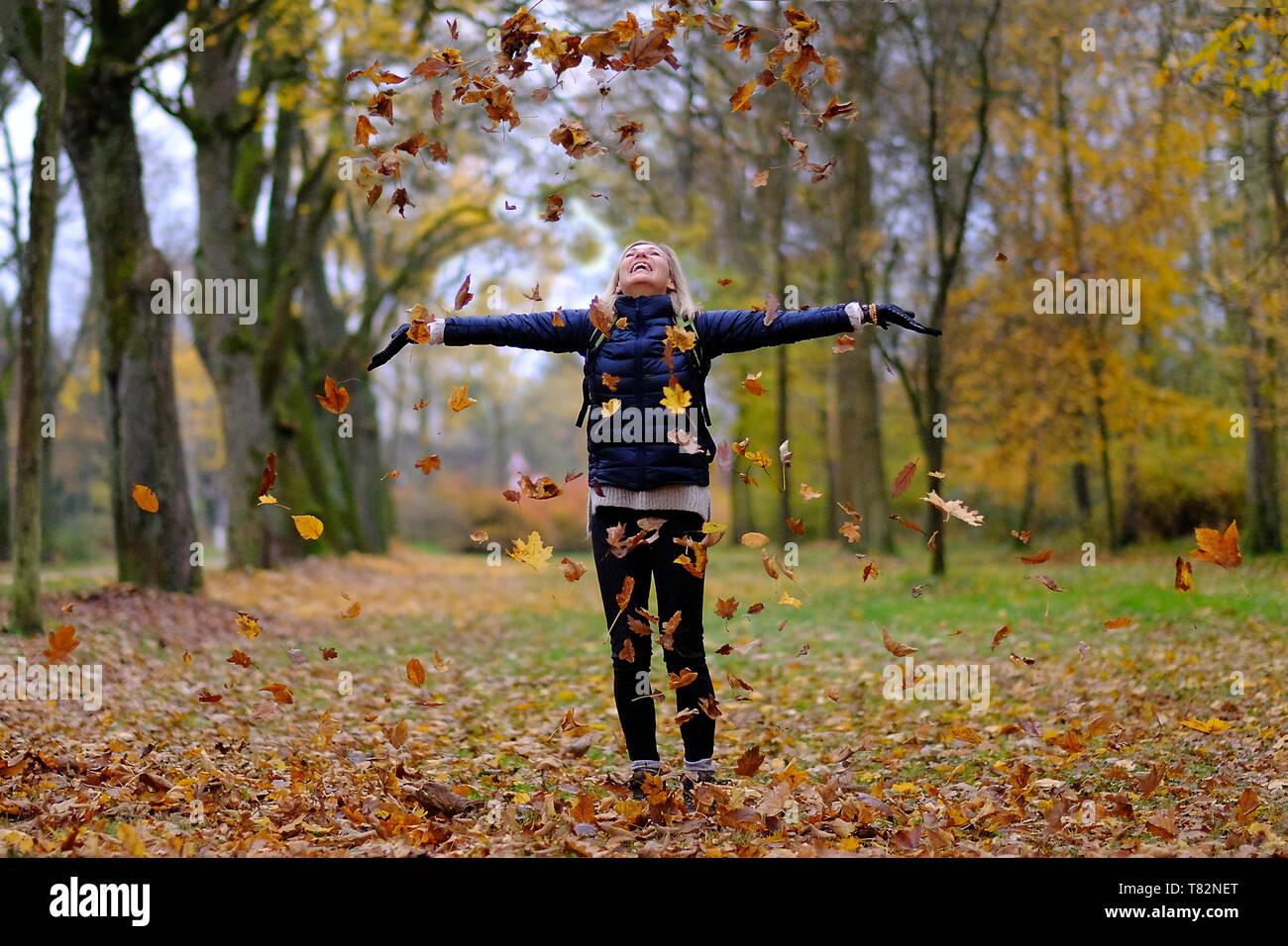 Junge Frau werfen bunte Blätter im Herbst in der Luft Stockbild