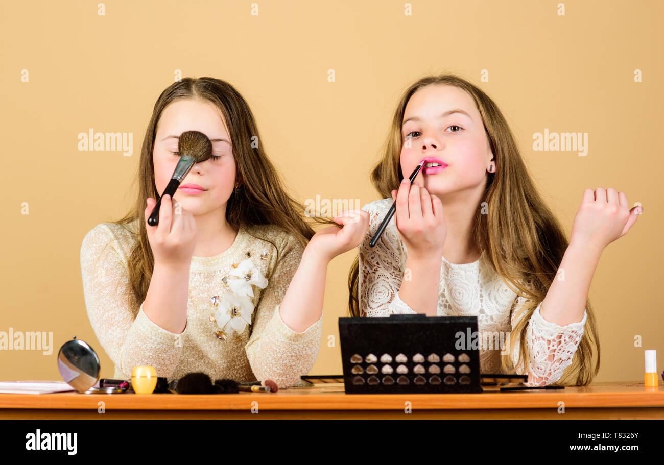 Experten in der Kosmetik. Süße Schönheit Modelle tragen Gesichtskosmetik. Kleine Mädchen Anwendung Dekorative Kosmetik mit Make-up-Pinsel. Kleine Kinder malen Gesichter mit Farbe Kosmetik. Stockbild