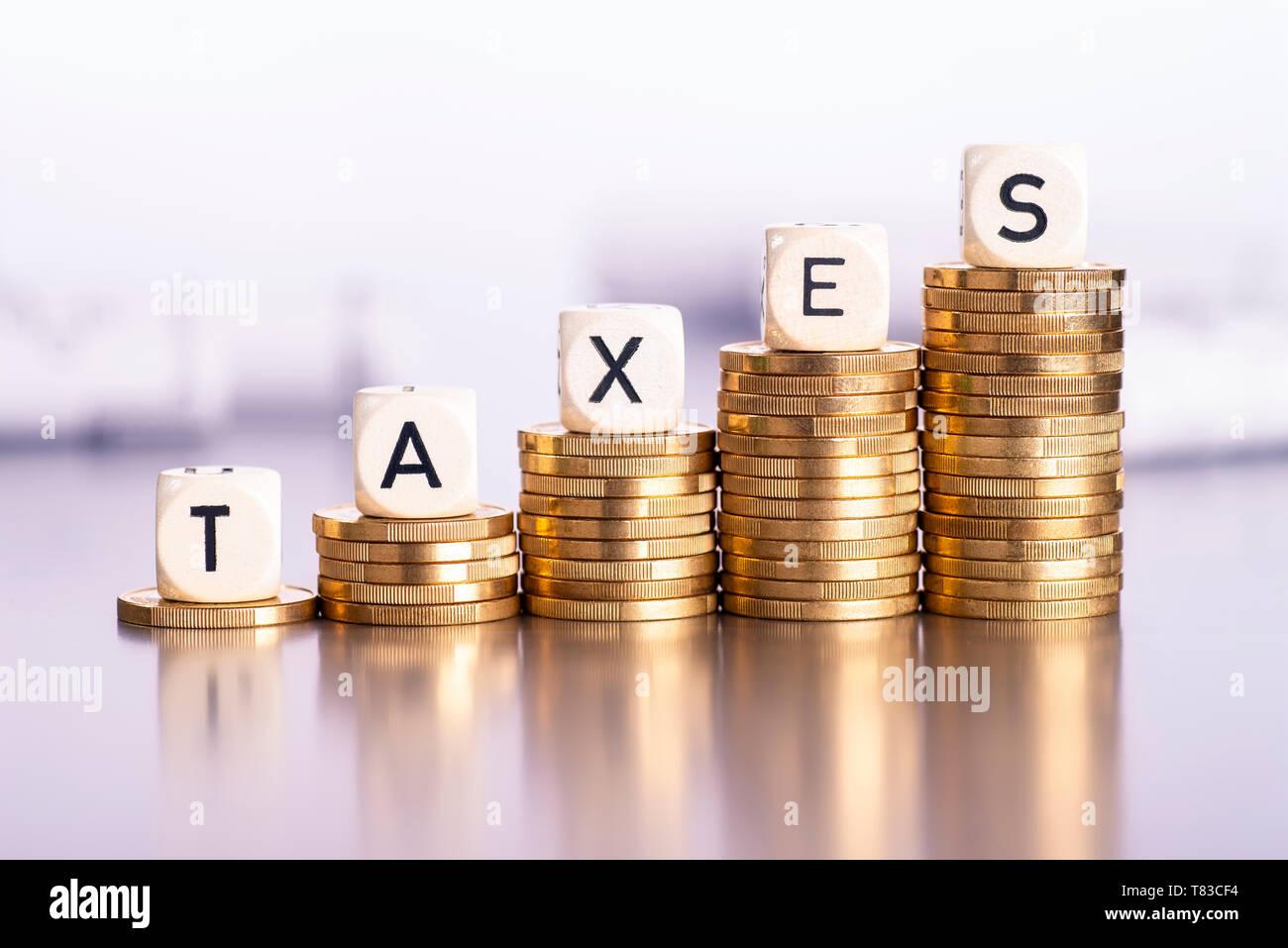 Steigende Stapel von Münzen mit dem Wort steuern Stockfoto