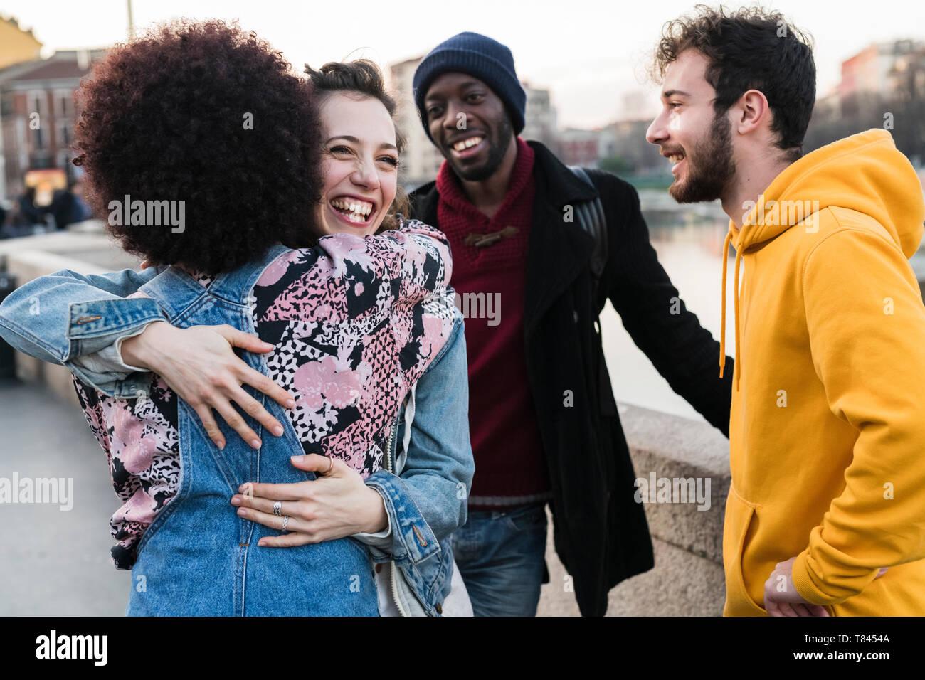 Vier weiblichen und männlichen Freunden reden und Umarmen auf Stadt canal Waterfront Stockfoto