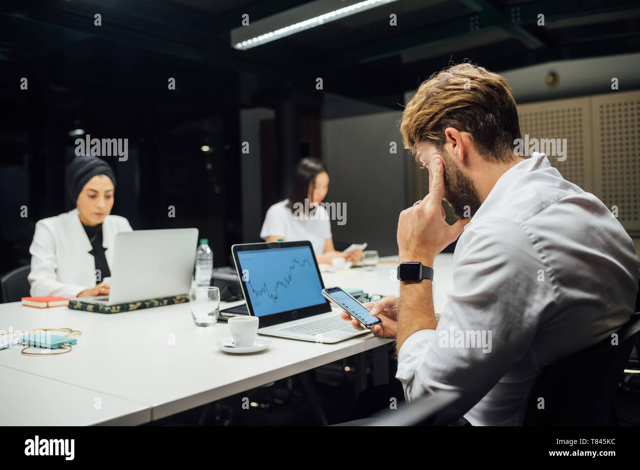 Geschäftsfrau auf Laptops und Smartphones am Konferenztisch Stockfoto