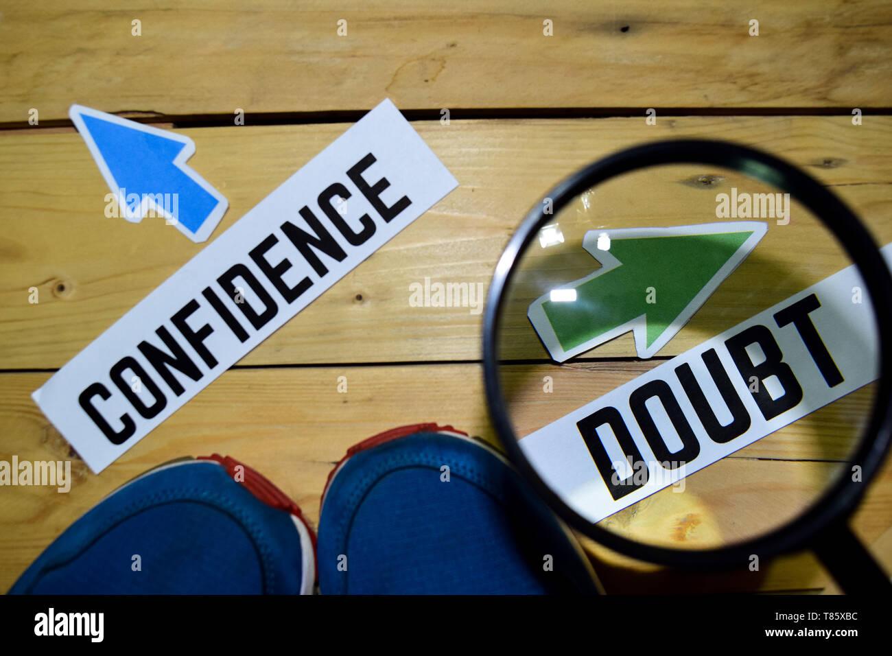 Vertrauen oder Zweifel entgegengesetzte Richtung Zeichen in Lupe mit Sneakers und Brillen auf Holz vintage Hintergrund. Wirtschaft und Bildung Konzepte Stockbild