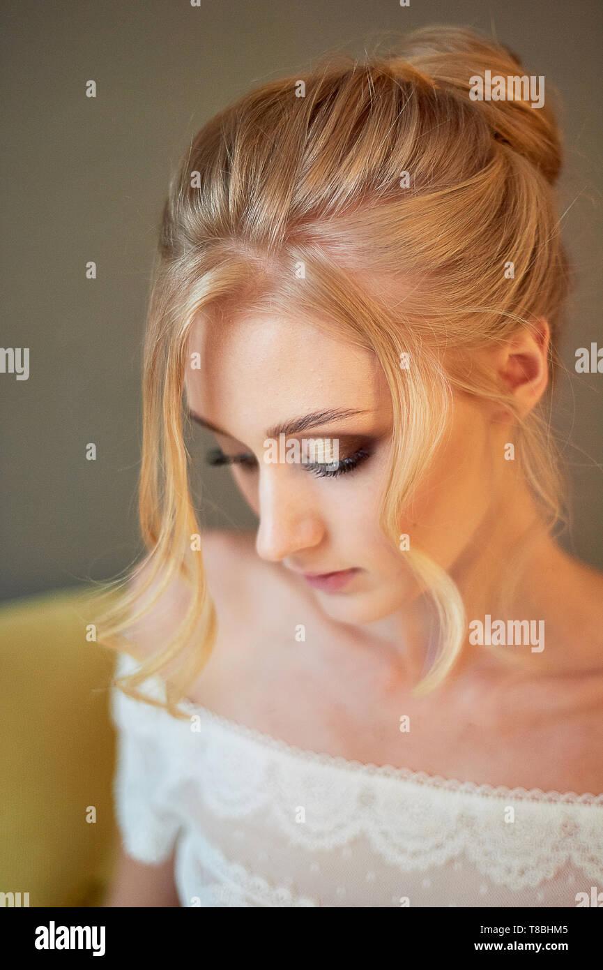 Porträt einer schöne Miniatur Braut in einem Spitzen Kleid. Haar mit Locken. Schwerpunkt in Make-up auf den Augen. Blond. Stockfoto