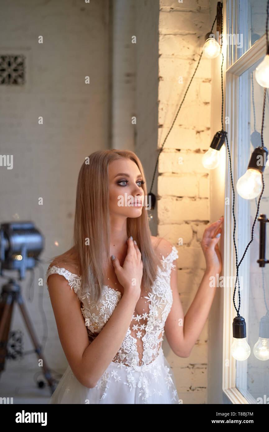 Porträt einer wunderschönen Braut in einem Spitzen Kleid. Make-up Smokey Eyes, Betonung der Augen. Lange fließende Haar. Stockfoto