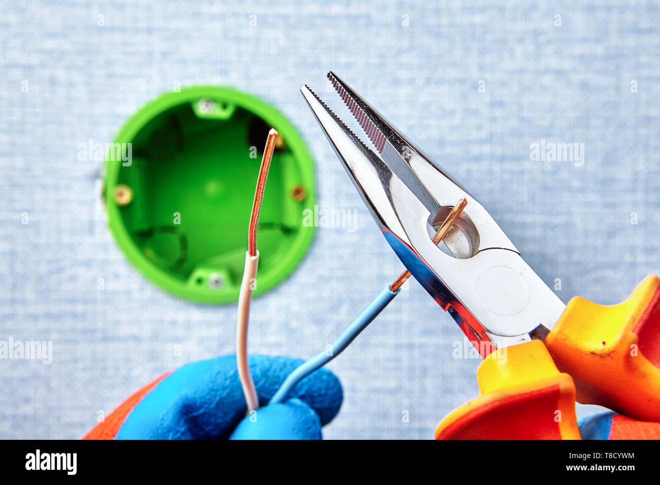 Worker ist Schneiden von Kupfer Verkabelung mit einer Schnabelzange während der Montage runde elektrische Feld, elektrische Arbeit. Stockbild