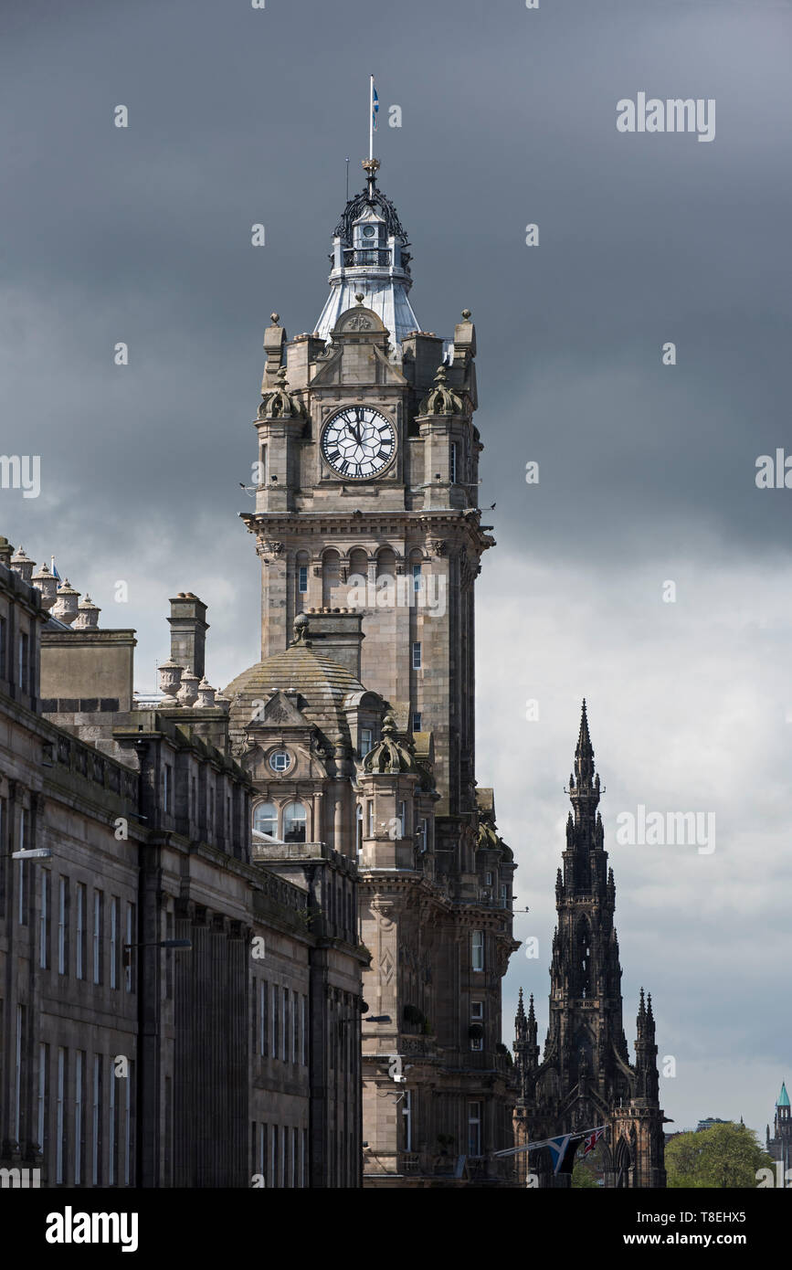 Der uhrturm der Balmoral Hotel an der Princes Street mit dem Scott Monument hinter einer bedrohlichen Himmel in der Ferne, Edinburgh, Schottland, Großbritannien und. Stockbild
