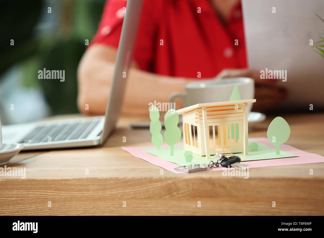 Papier Modell von Haus mit Schlüssel auf dem Tisch im Büro von Real estate agent Stockbild