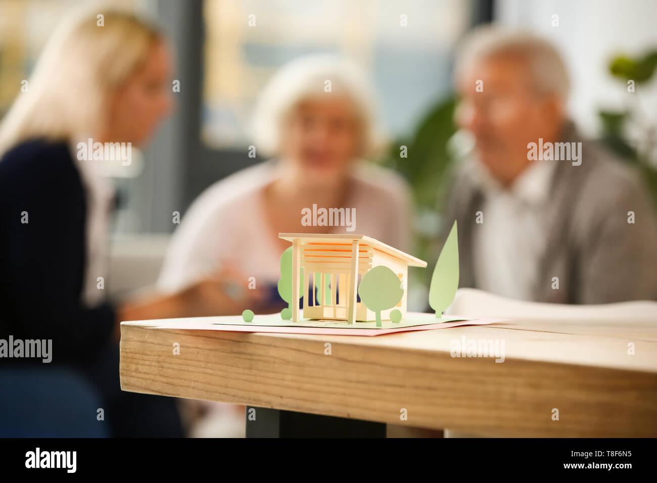 Papier Modell des Haus am Tisch im Büro von Real estate agent Stockbild