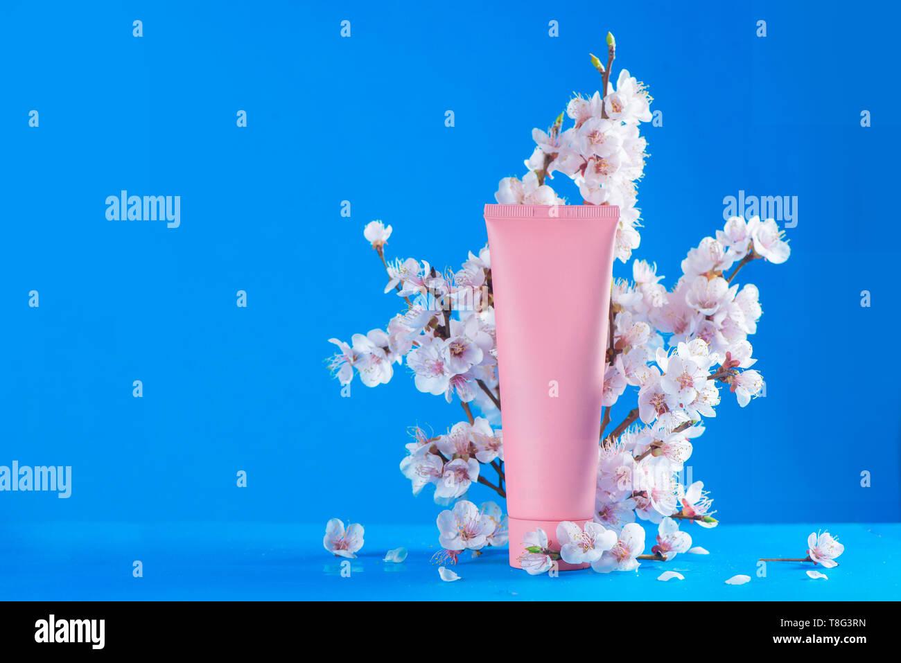 Cherry Blossom Kosmetik header. Rosa Creme Tube mit Frühling Blumen auf einem Himmel blauer Hintergrund mit kopieren. Stockbild