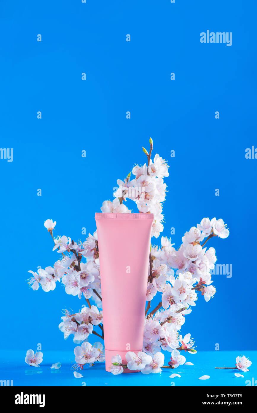 Cherry Blossom Kosmetik Konzept. Rosa Creme Tube mit Frühling Blumen auf einem Himmel blauer Hintergrund mit kopieren. Stockbild
