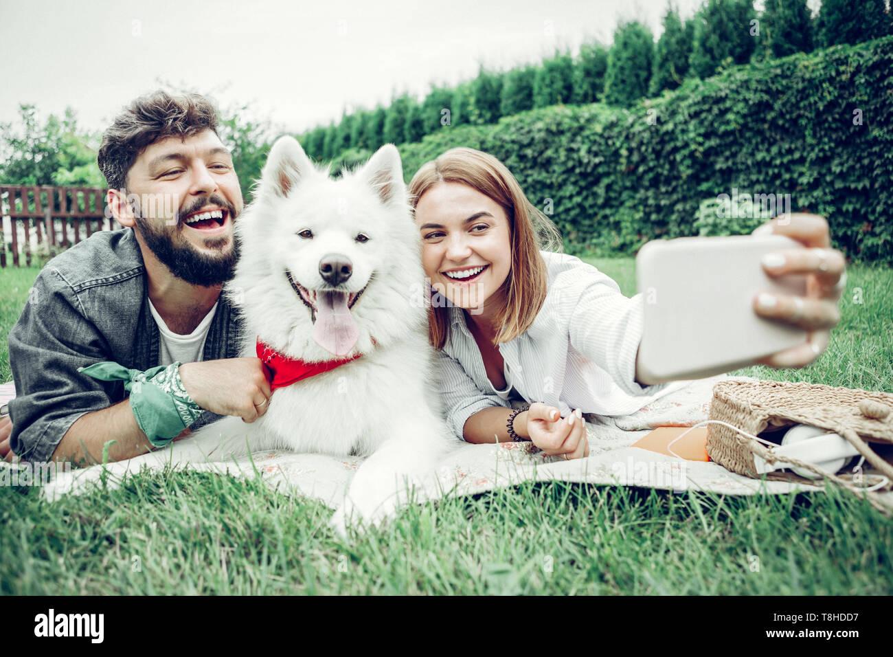 Schönes Paar verbringt Zeit mit einem Hund und unter selfie. Stockbild