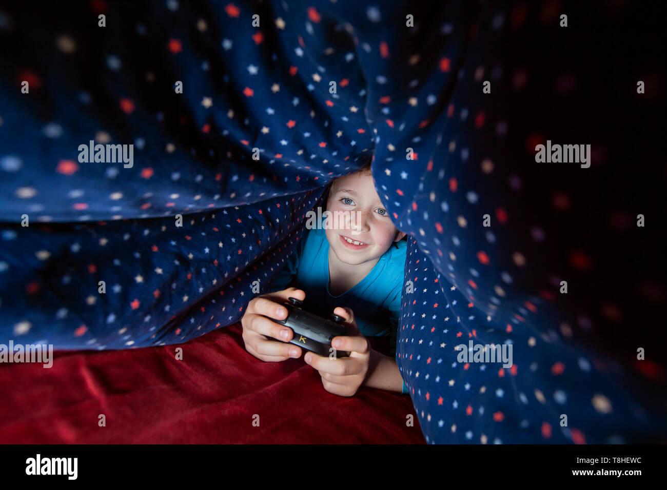 Junge, 8 Jahre, sectretly spielen, computer spiel im Bett Stockbild