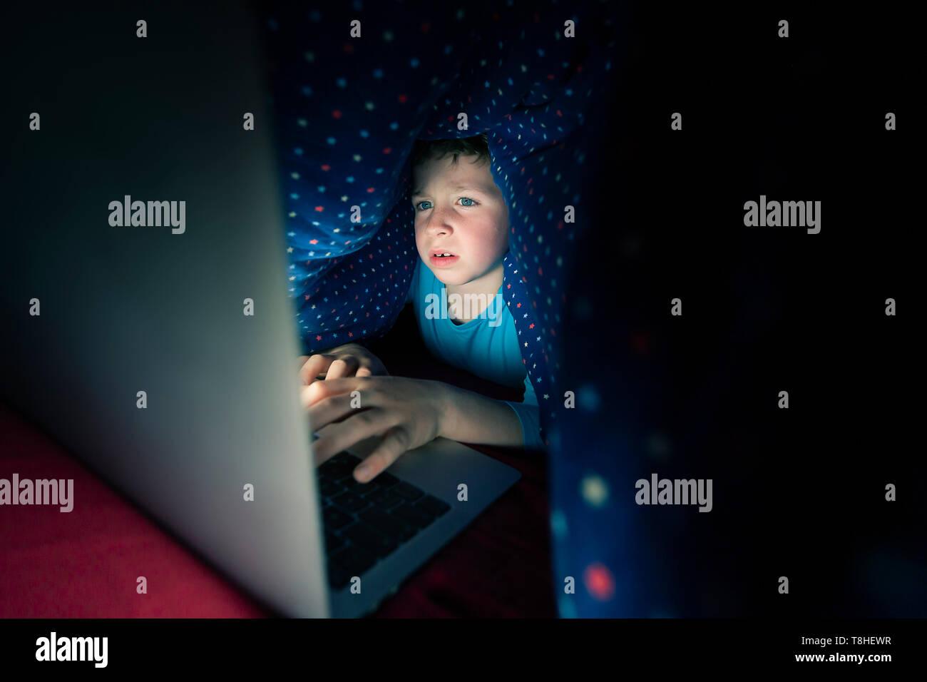 Junge heimlich über das Internet im Bett Stockbild