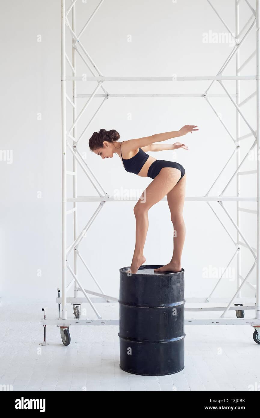 Anmutige gymnast steht auf einem hohen schwarz Barrel, macht komplexe Formen. Sport, Fitness, Stretching. Stockfoto