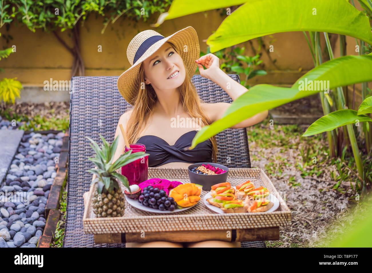 Junge Frau essen Frühstück in einem Sessel auf einem Tablett mit Obst, Brötchen, Avocado Sandwiches, smoothie Schüssel am Pool. Sommer gesunde Ernährung, vegan Stockfoto