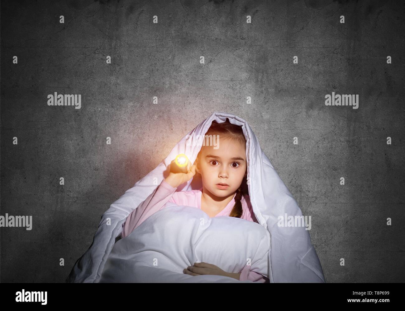 Verängstigten Mädchen mit der Taschenlampe unter der Bettdecke Stockbild