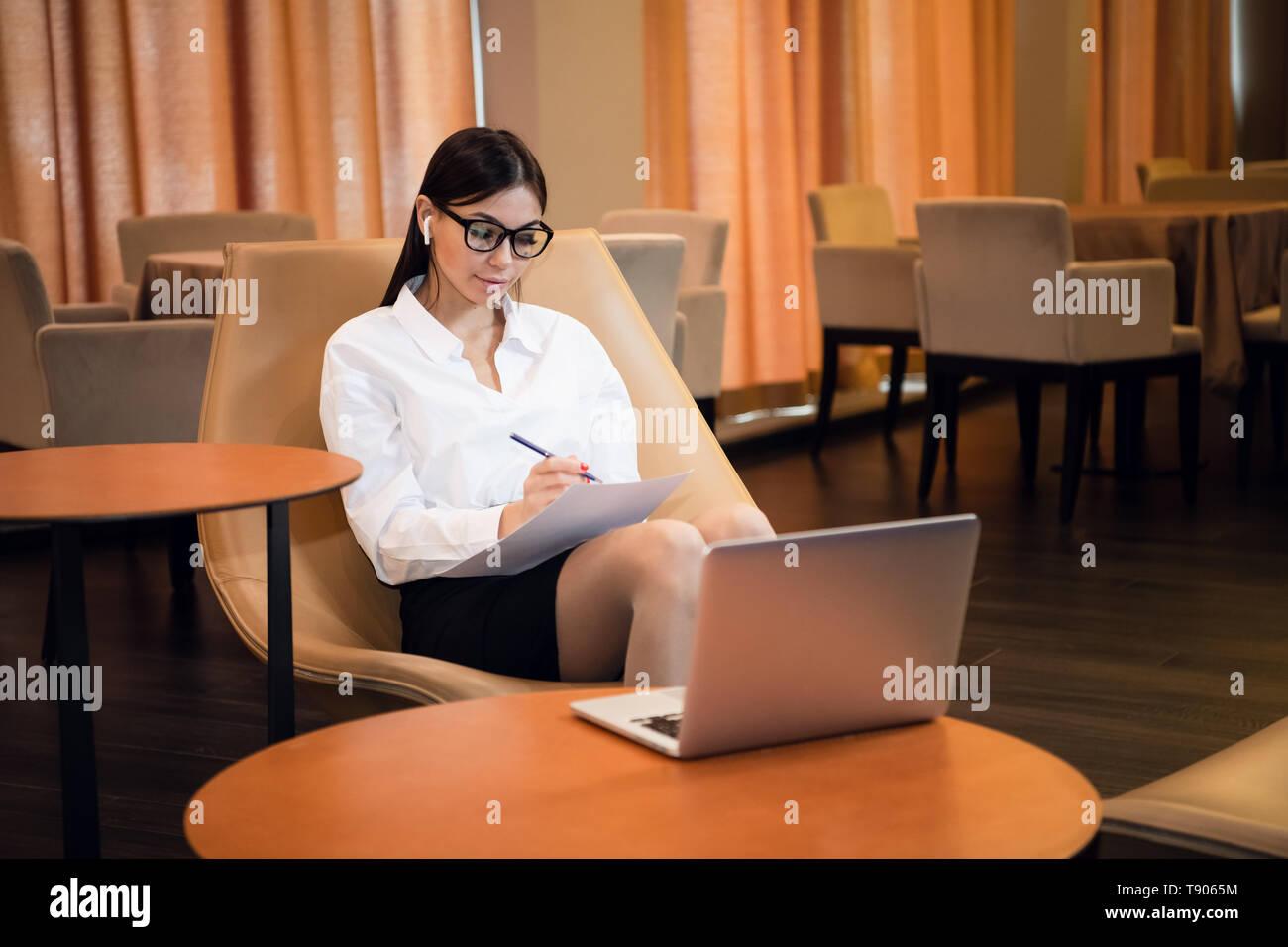 Schöne junge geschäftsfrau Arbeiten am Computer in der Hotellobby Stockfoto