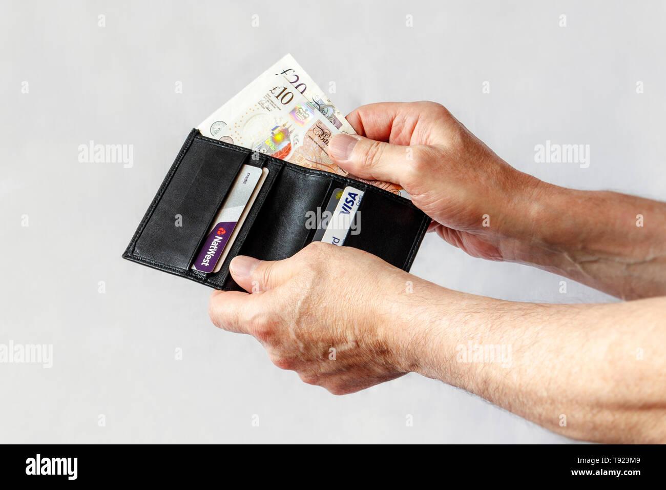Nahaufnahmen der Hände des Menschen unter 10 lbs und 20 lbs Hinweis von einem schwarzen Lederetui, auch mit Kreditkarten Stockfoto