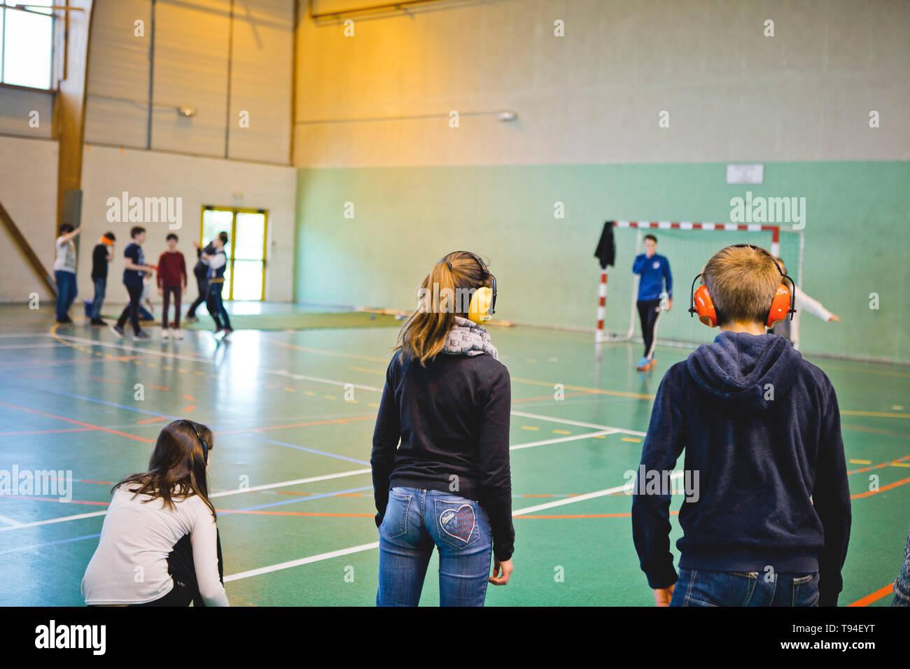 Behinderung Bewusstsein in der Schule. Junge Schüler Schülerinnen und Schüler üben ein Sport mit Ohrenschützer, um herauszufinden, wie es ist taub zu werden. Stockfoto