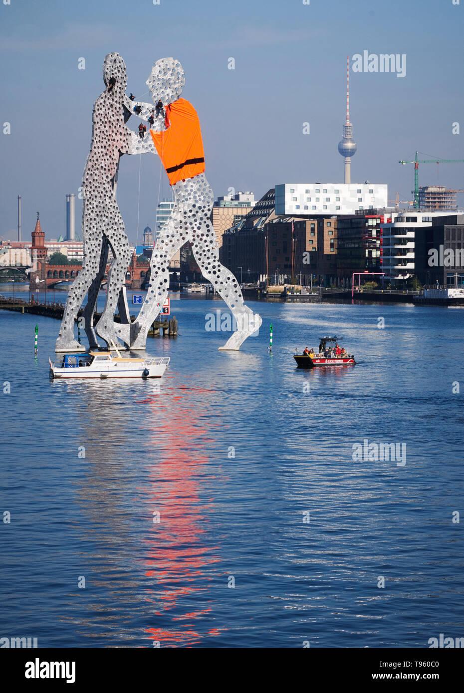 Berlin, Deutschland. 17 Mai, 2019. Aktivisten hängen von der Gestaltungsarbeit Molecule Man von uns Bildhauer Jonathan Borofsky in der Spree und haben eine der Abbildungen auf einer übergroßen Schwimmweste. Sie protestierten gegen die europäische Flüchtlingspolitik. Quelle: Annette Riedl/dpa-Zentralbild/dpa/Alamy leben Nachrichten Stockfoto