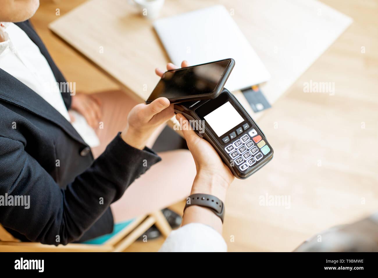Unternehmer zahlen mit kontaktlosen Smart Phone, während im Cafe sitzen, Nahaufnahme Stockfoto