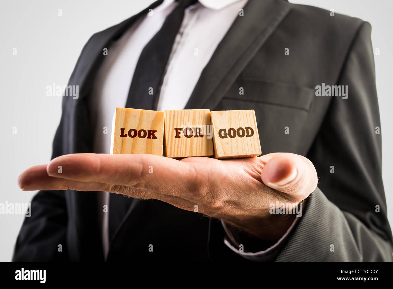 Nahaufnahme der männlichen Hand hält drei hölzerne Würfel mit einem Blick für guten Text. Konzept der persönlichen Einstellung zu leben und Leben Herausforderungen. Stockbild