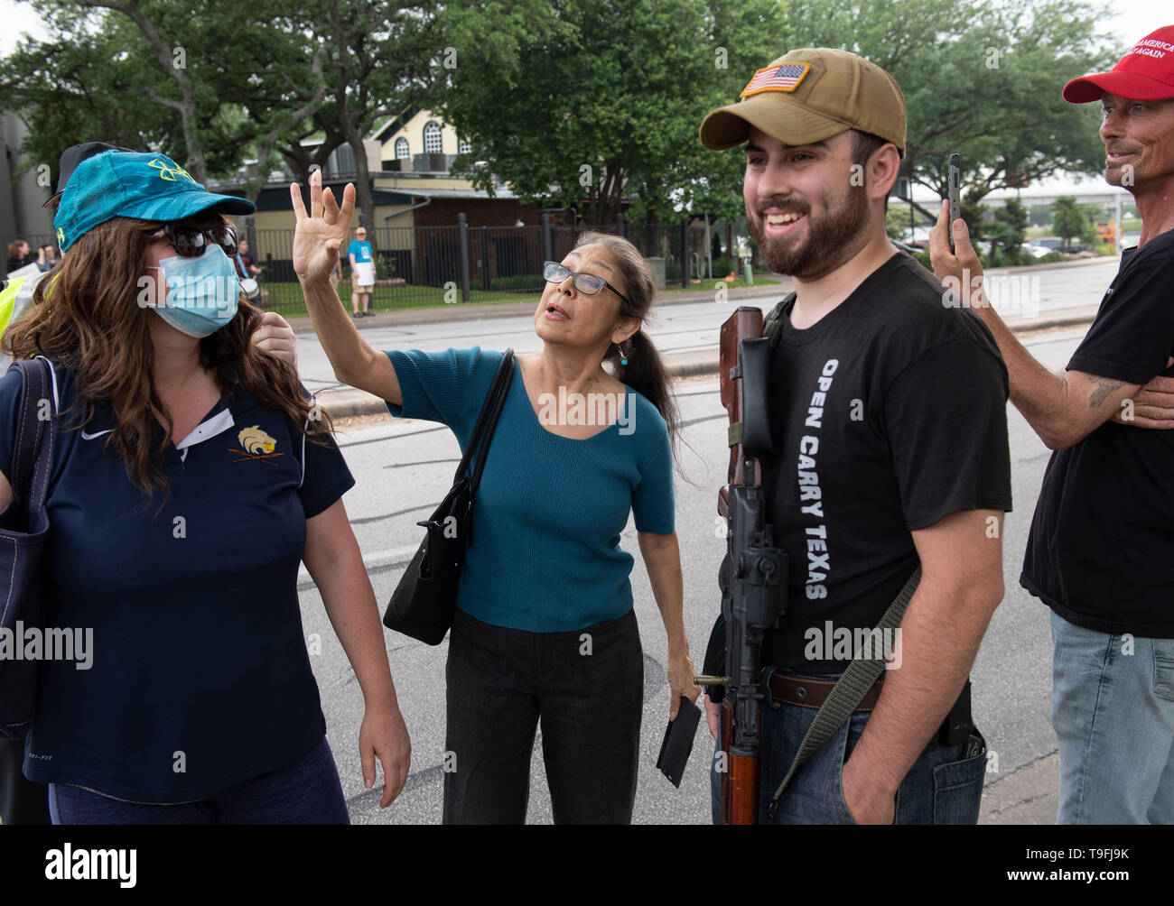 Ein Anhänger von Ilhan Omar (Mitte) konfrontiert anti-muslimische Demonstranten, einige öffnen die Waffen legal, außerhalb eines Austin, Texas, hotel, in dem die umstrittenen Muslimischen Kongressabgeordnete an einer Stadt sprach-weiten iftar Abendessen. Stockbild