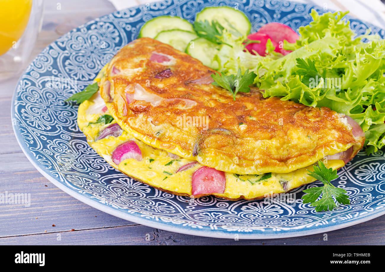 Frühstück. Omelett mit Radieschen, roten Zwiebeln und frischem Salat auf blauen Platte. Frittata - italienische Omelette. Stockfoto