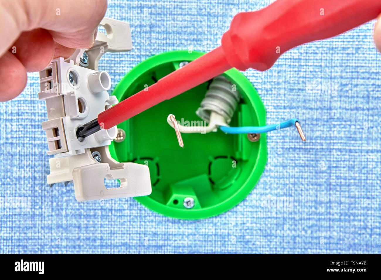 Handwerker verdreht Schraube in neuen europäischen Standard runde Schaltkasten mit dielektrischen Schraubendreher, elektrische Arbeit. Stockbild
