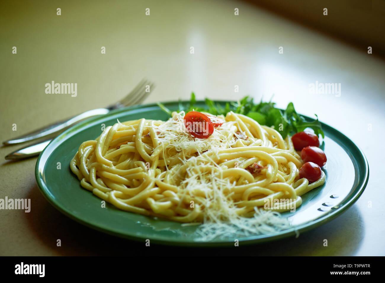 Pasta Carbonara mit geriebenem Parmesan und Cherry Tomaten, dekoriert mit Rucola. italienischen Mittagessen. Stockbild