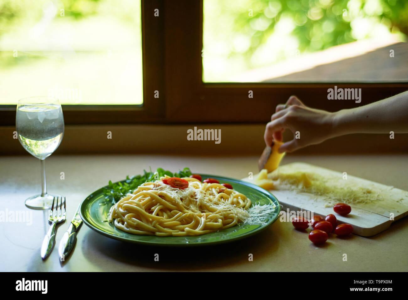 Pasta Carbonara mit geriebenem Parmesan und Cherry Tomaten, dekoriert mit Rucola. italienischen Mittagessen. Die Hand einer Frau setzt ein Stück Käse. Stockbild