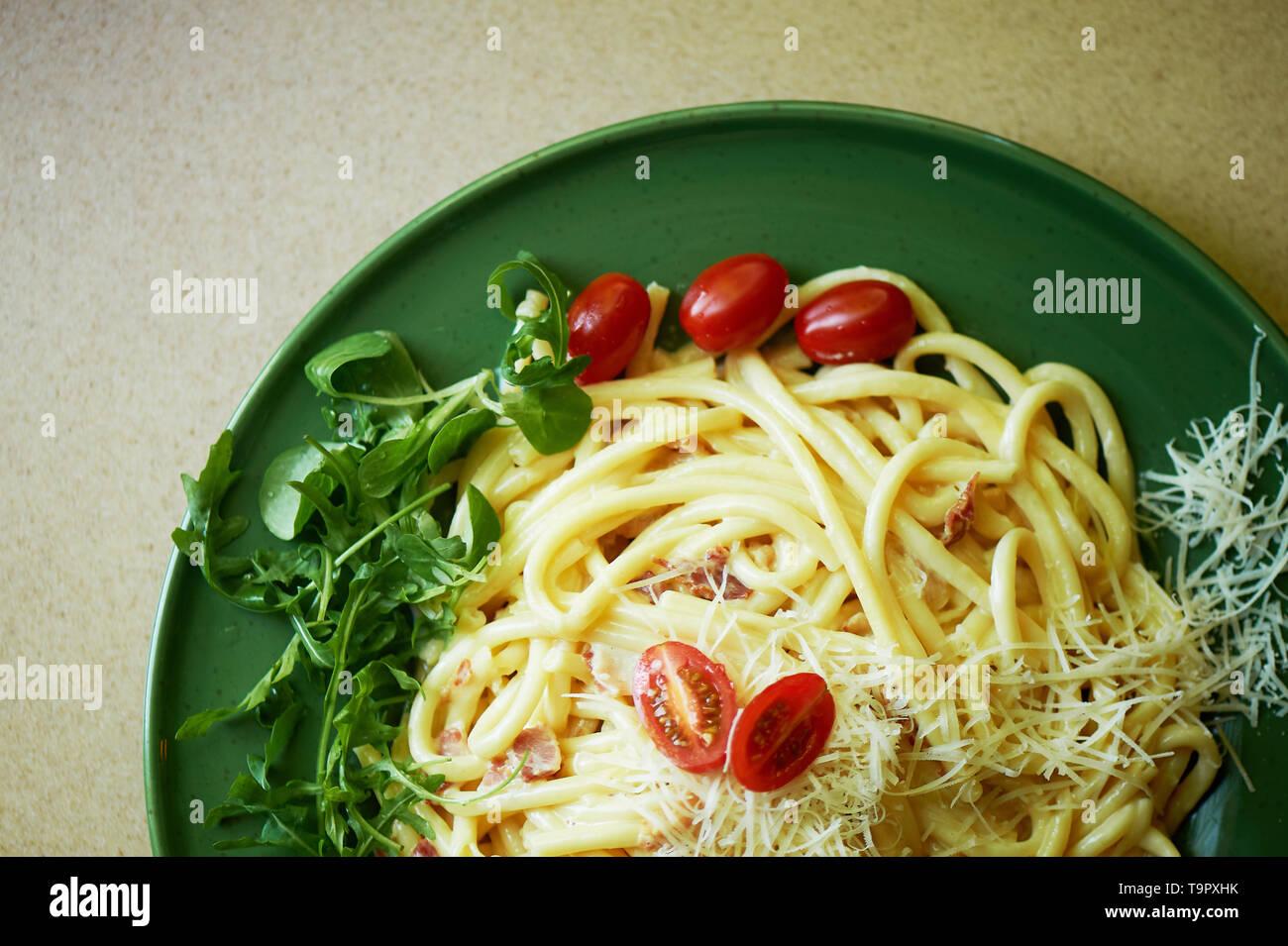 Pasta Carbonara mit geriebenem Parmesan und Cherry Tomaten, dekoriert mit Rucola. Italienisches Mittagessen. Stockbild