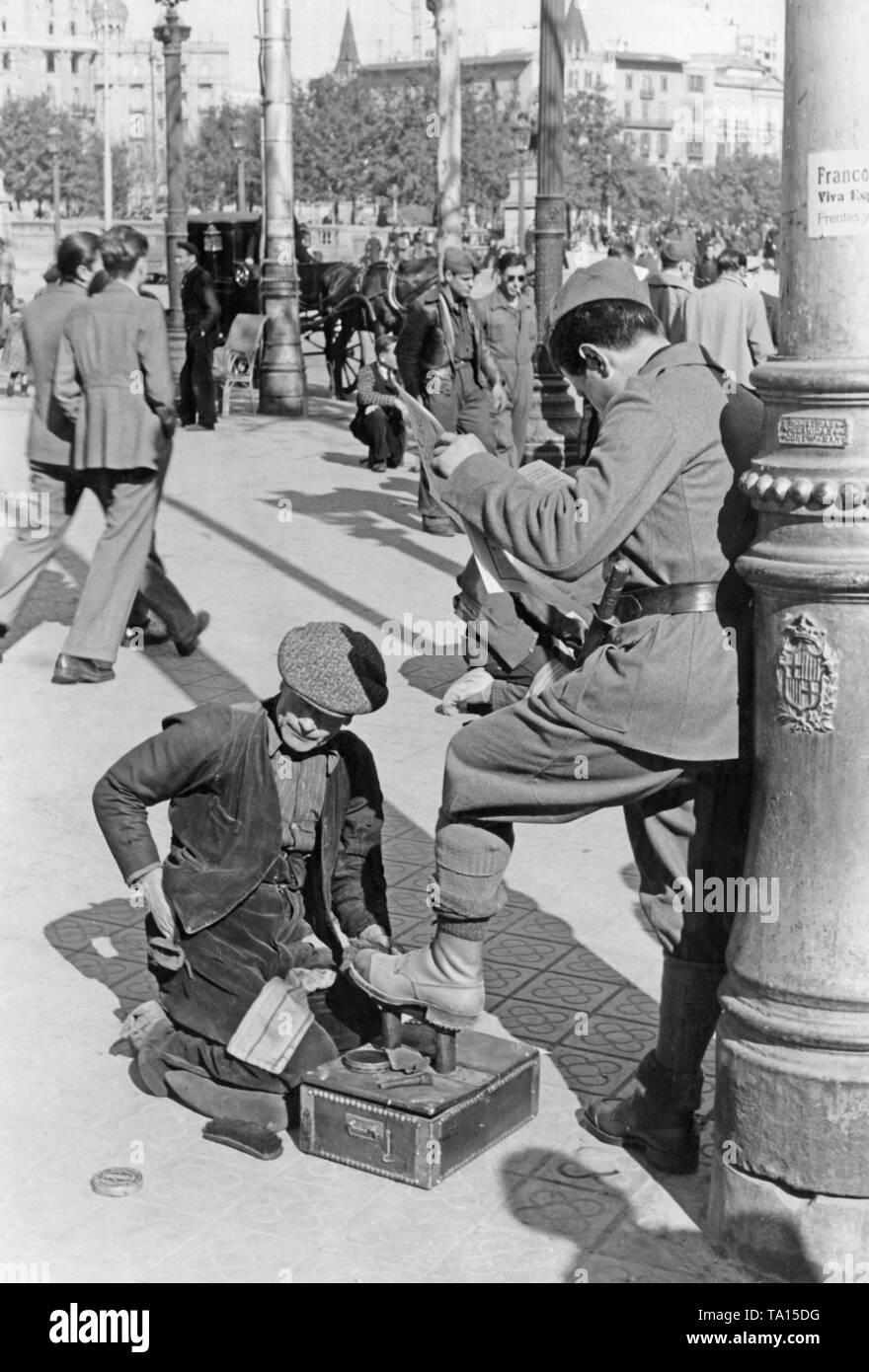 Ein spanischer Soldat lässt einen Mann sauber seine Schuhe, während er eine Zeitung lesen, vor einer Laterne auf der Rambla (Promenade im Zentrum) in Barcelona?? Katalonien, Spanien im März 1939, nach der Eroberung der Stadt durch General Francisco Franco im Januar, 1939. Im Hintergrund, flaneure und Soldaten. Auf der Laterne, einen Anruf von Franco für die Einwohner von Barcelona. Unten auf dem gusseisernen Laterne, das Wappen von Barcelona. Stockfoto