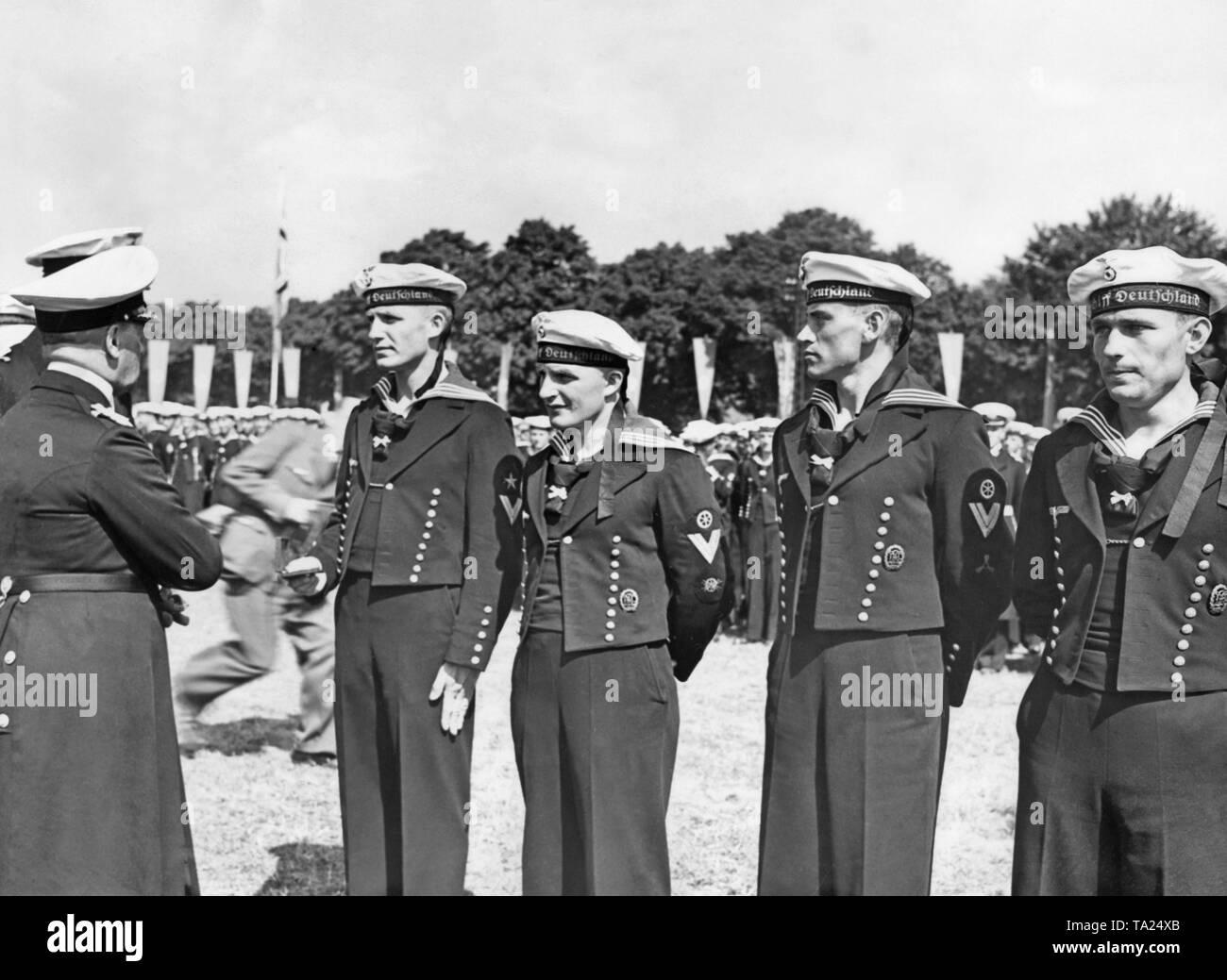 Grand Admiral Erich Raeder (links) ehrt Segler (Befreiung der Seeleute) der Deutschen cruiser 'Deutschland' der Kriegsmarine, die im Spanischen Bürgerkrieg gekämpft, in Doeberitz in der Nähe von Berlin am 5. Juni 1939. Im Hintergrund, ein Fotograf huscht durchs Bild. Stockbild