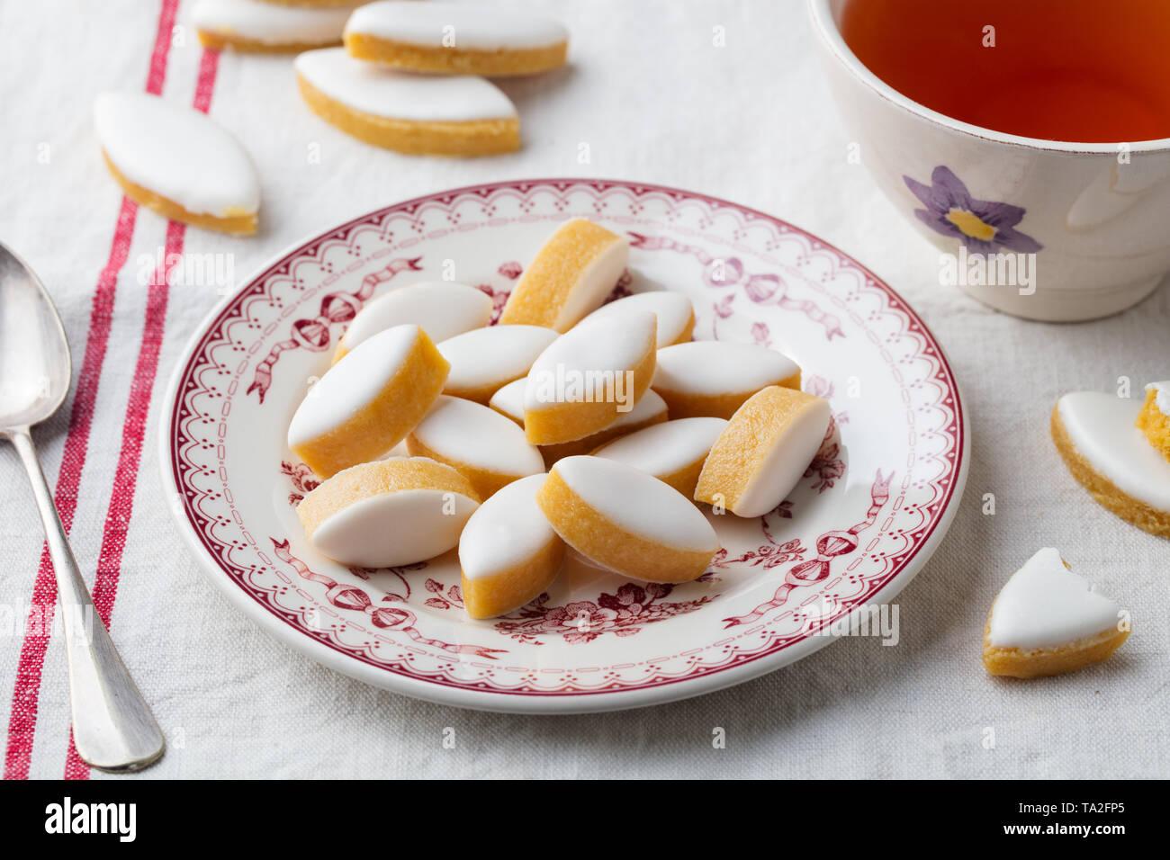 Calissons auf einem Teller. Traditionelle französische Provence Süßigkeiten mit Tasse Tee. Stockbild