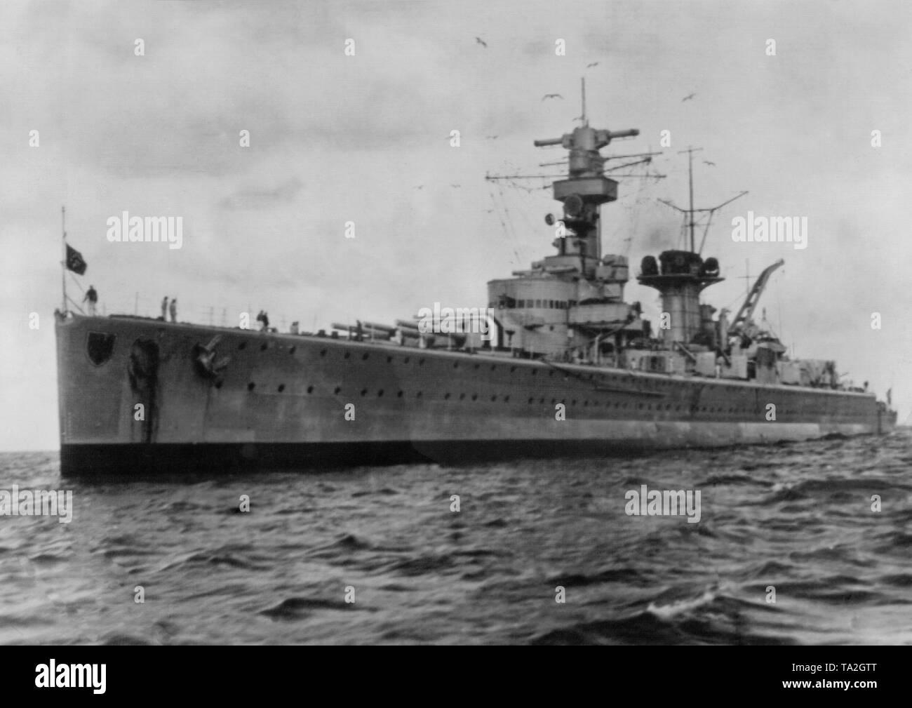 Foto der teilweise zerstörten Heavy Cruiser 'Deutschland' bei der Einfahrt in den Hafen von Wilhelmshaven an der Nordsee im Juni 1937. Die navy Battle Flag weht an der Vorderseite des Bogens. Dahinter, den Turm mit drei Gun Barrel (Kaliber 28 cm). Stockbild