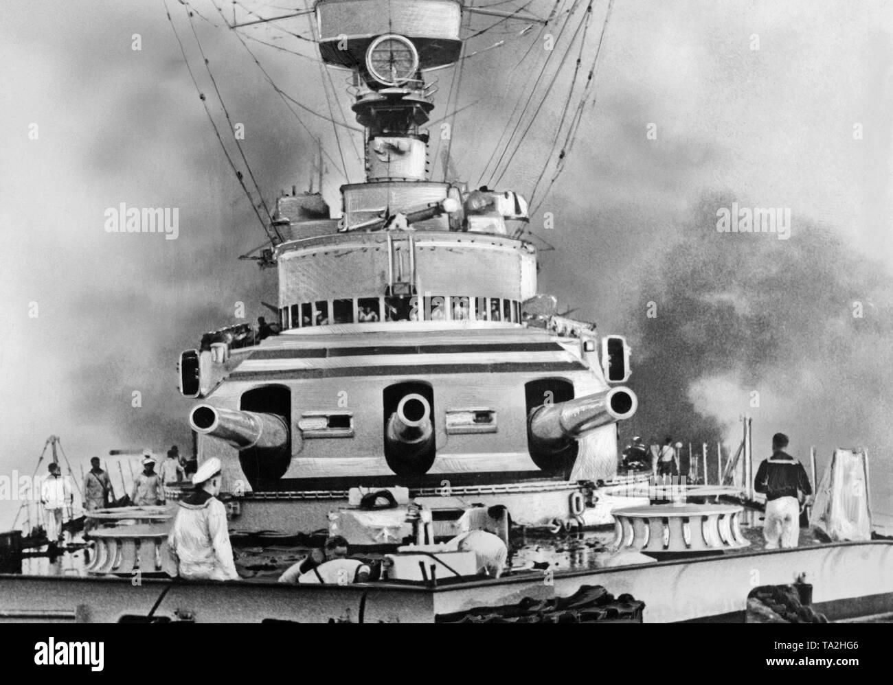 Die teilweise schwere Kreuzer Deutschland kurz nach der Bombardierung zerstört von zwei Republikanische Kampfflugzeuge im Mai 1937 vor der Balearen Insel. Direkt neben der vordere Geschützturm (drei 28 cm Schnellfeuerkanone) steigen Rauchschwaden. Bevor es, Seeleute sind in Brand-bekämpfung. Stockbild