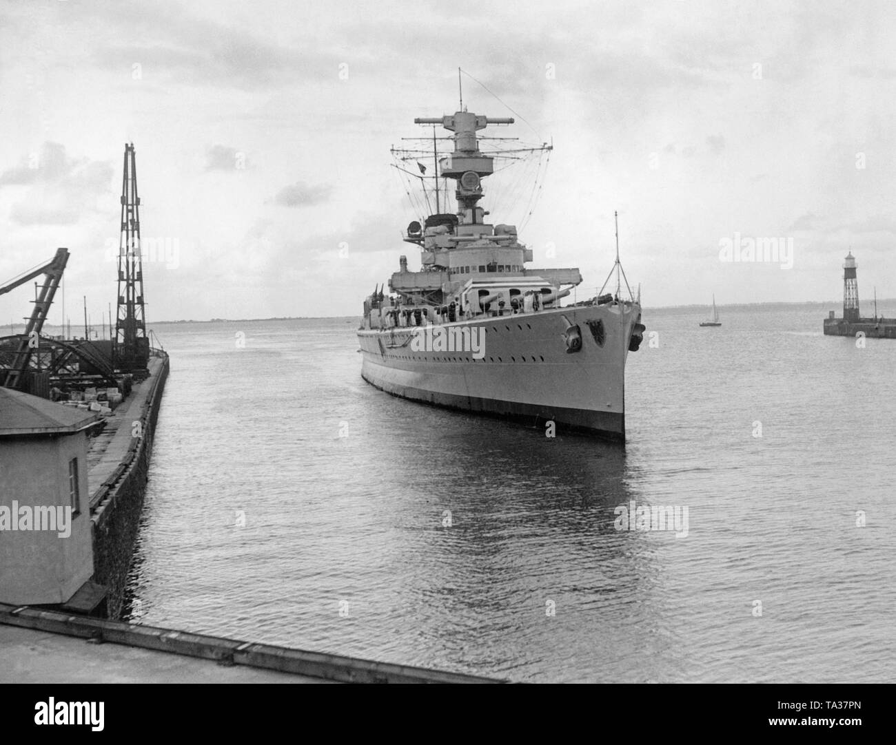 Foto der teilweise zerstörten Heavy Cruiser 'Deutschland' bei der Einfahrt in den Hafen von Wilhelmshaven an der Nordsee im Juni 1937. Nach rechts und links, die Hafenanlagen. Stockbild