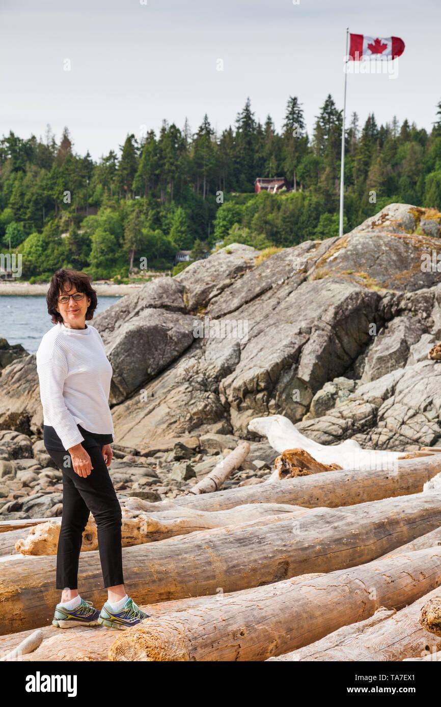 Extrem jugendlich Großmutter gehen auf Treibholz Protokolle an der Sunshine Coast in British Columbia Kanada Stockbild