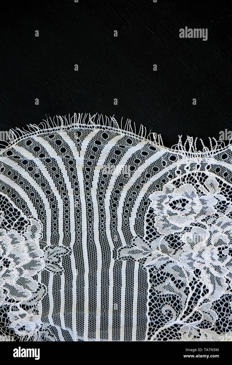 Weiße Spitze auf schwarzem Hintergrund. Die Textur ist in der Nähe. Stockbild