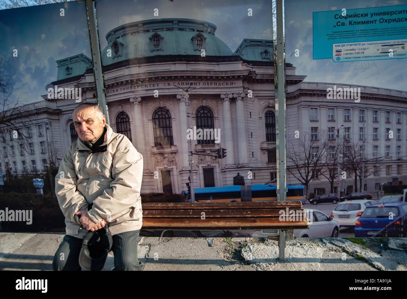 Ein bulgarischer Mann wartet an einer Bushaltestelle mit einem Bild von der Universität Sofia hinter ihm. Bulgarien mit einer alternden Bevölkerung ist der am schnellsten schrumpfenden Land Stockbild